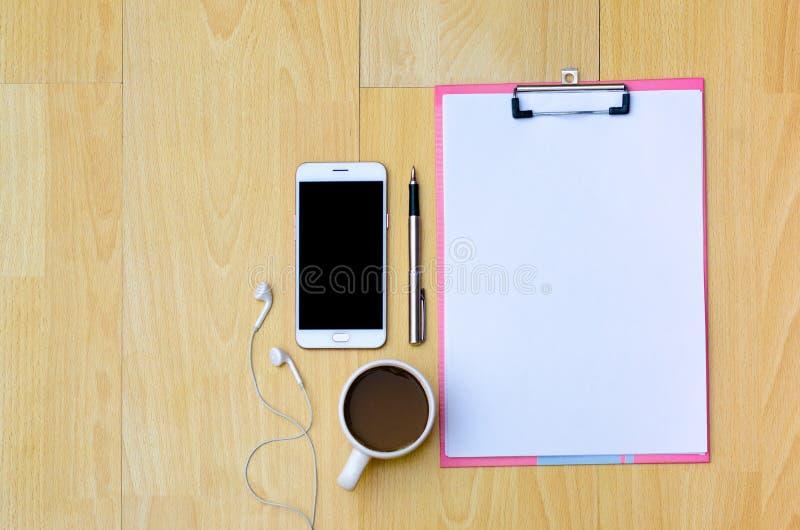 Copos de café do telefone do modelo, papel de nota dos fones de ouvido colocado em uma vista superior de madeira fotografia de stock royalty free