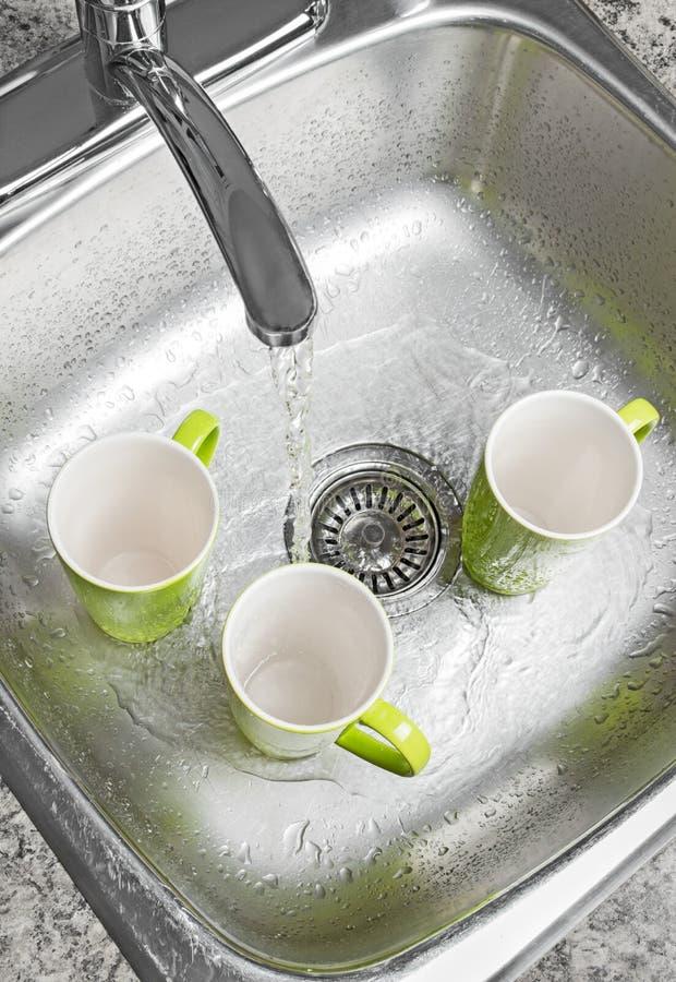 Copos de lavagem na banca da cozinha fotos de stock royalty free