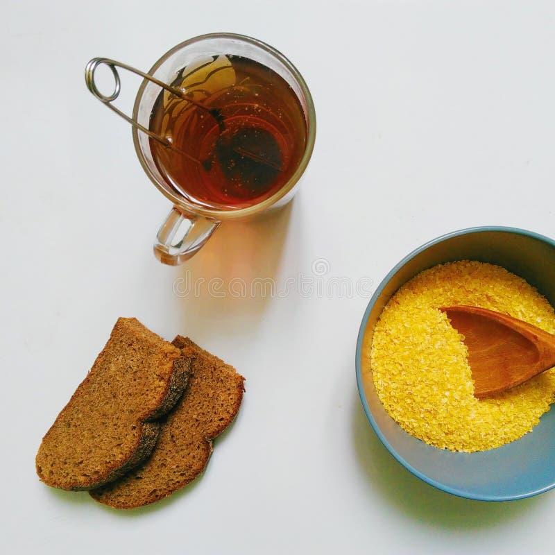 copos de maíz en una placa, una taza de té negro y dos rebanadas de pan en un fondo blanco imagenes de archivo