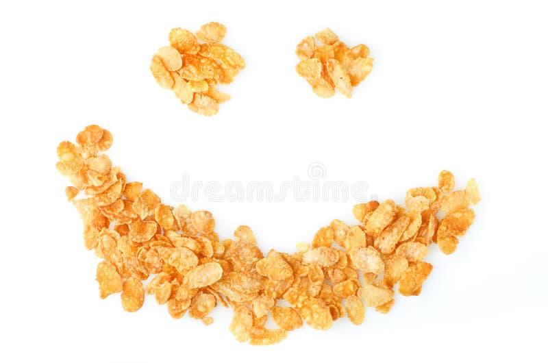 Copos de maíz frescos amarillos secos del cereal de desayuno en sonrisa en b blanco imagen de archivo libre de regalías