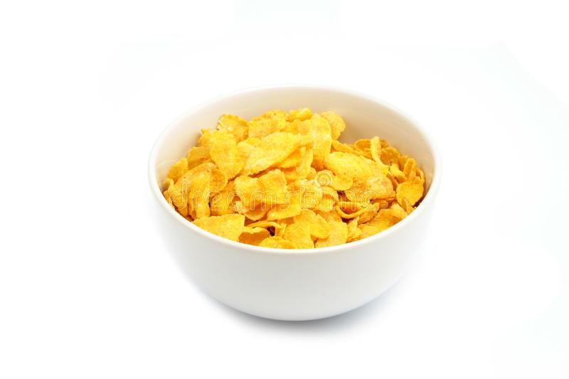 Copos de maíz o cereal en el fondo blanco fotos de archivo