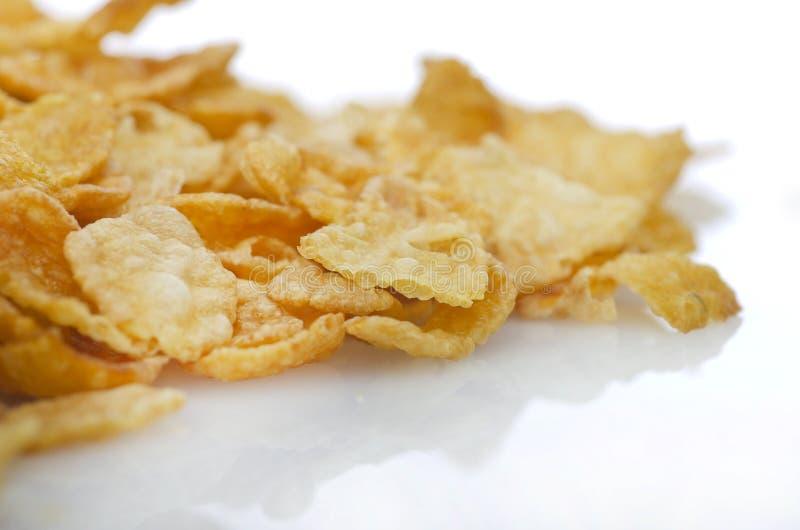 Copos de maíz secos del cereal de desayuno en el fondo blanco fotografía de archivo