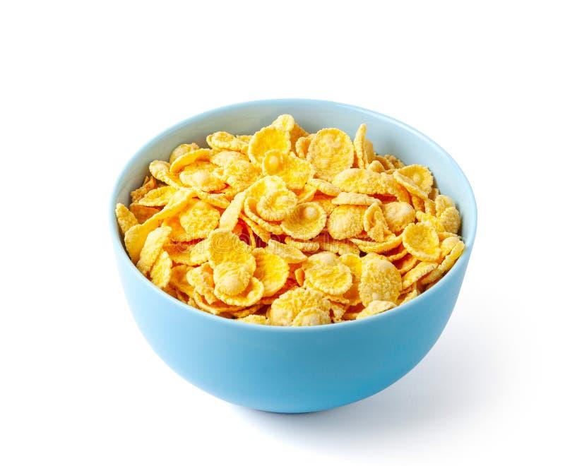 Copos de ma?z secos del desayuno Placa azul por completo del cereal Aislado en el fondo blanco fotografía de archivo