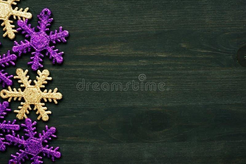Copos de nieve amarillos y violetas como decoración de la Navidad en un fondo de madera oscuro Copie el espacio fotografía de archivo