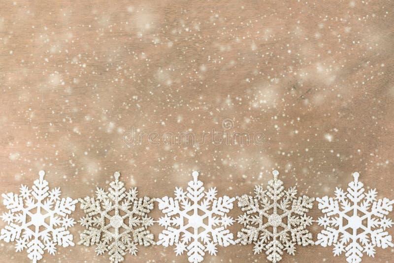 Copos de nieve blancos, de plata en el fondo de madera foto de archivo