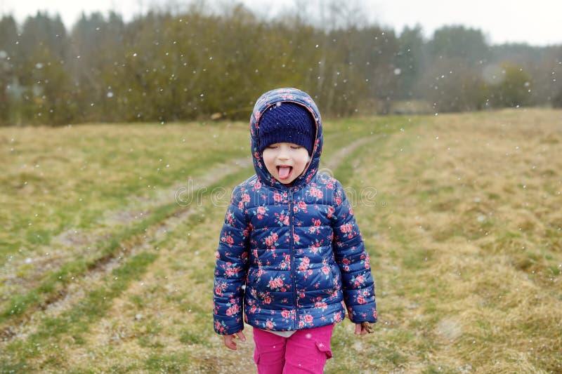 Copos de nieve de cogida de la niña linda primeros con su lengua el día del otoño imagen de archivo