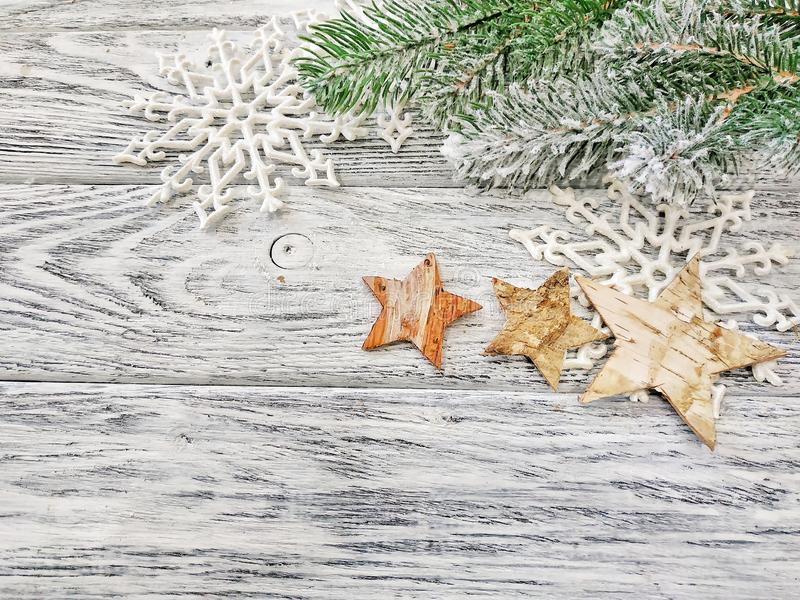 Copos de nieve del fondo de la Navidad, ramas del pino y estrellas en un fondo de madera imagenes de archivo