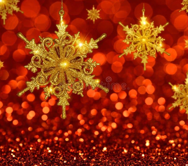 Copos de nieve del oro de la Navidad en fondo rojo fotos de archivo libres de regalías