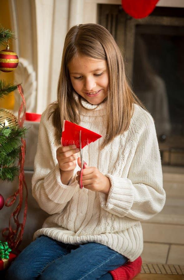 Copos de nieve del papel del corte de la muchacha para las decoraciones en la Navidad foto de archivo libre de regalías