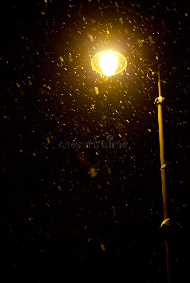 Copos de nieve que caen teniendo en cuenta la linterna foto de archivo libre de regalías