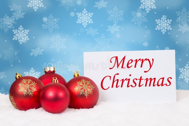 Copos de nieve rojos de la decoración de las chucherías de las bolas de la tarjeta de la Feliz Navidad fotos de archivo