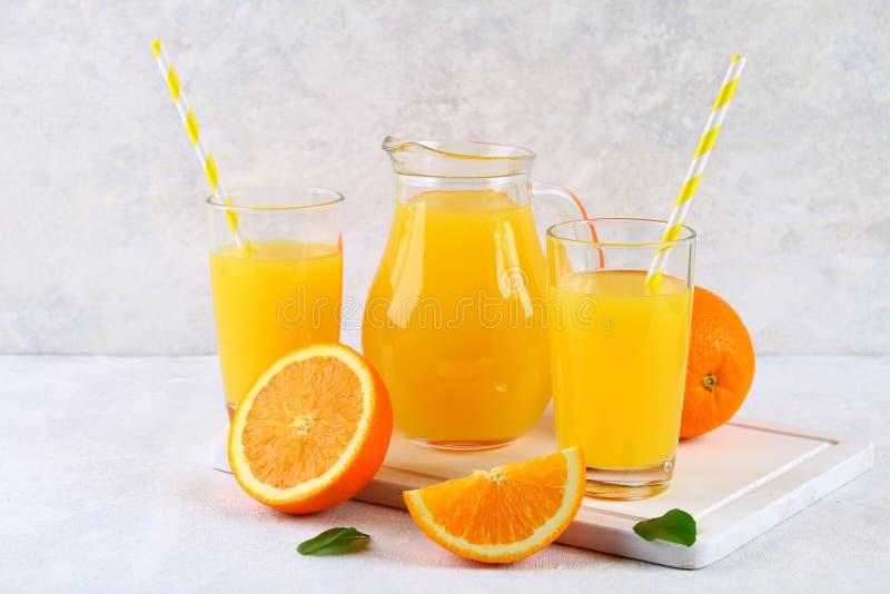 Copos de vidro e um jarro do suco de laranja fresco com fatias de tubos alaranjados e amarelos em uma luz - tabela cinzenta imagem de stock