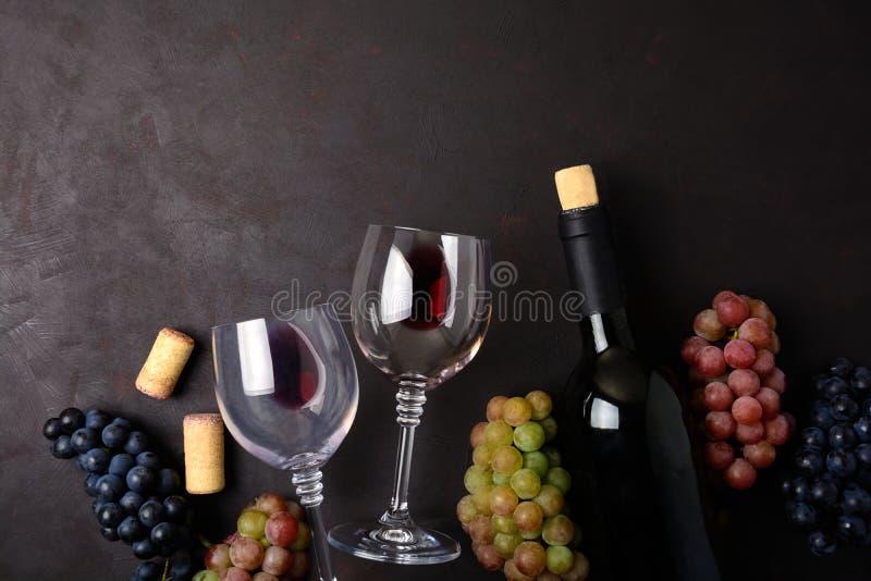 Copos de vinho com o vinho tinto, a garrafa, as uvas e as cortiça encontrando-se no fundo de madeira escuro Vista superior Config foto de stock