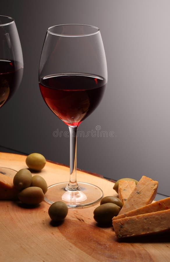 Copos de vinho com vinho tinto na madeira com queijo e azeitonas verdes Fundo do estúdio foto de stock royalty free
