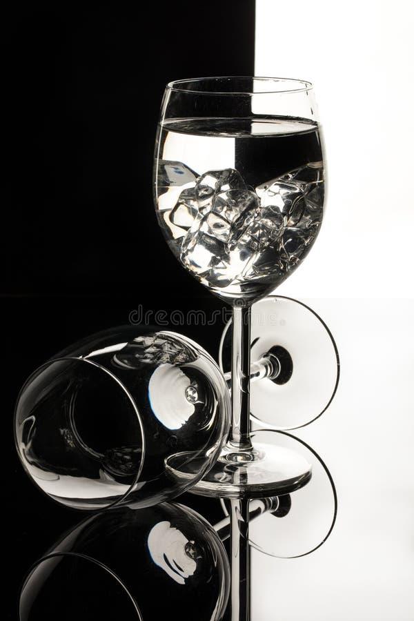 Copos de vinho em um fundo de vidro preto do estúdio imagem de stock royalty free