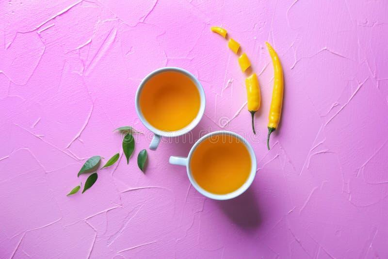 Copos do chá aromático quente com pimenta de pimentão amarela na tabela foto de stock
