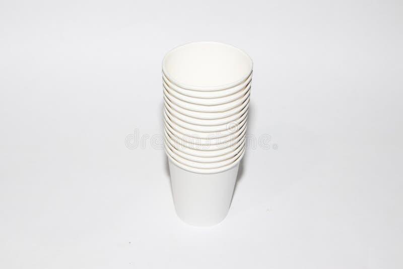 Copos do Livro Branco para o chá em um fundo branco Objetos isolados Delicadamente quente Utensílios de mesa descartáveis Pratos  imagem de stock royalty free
