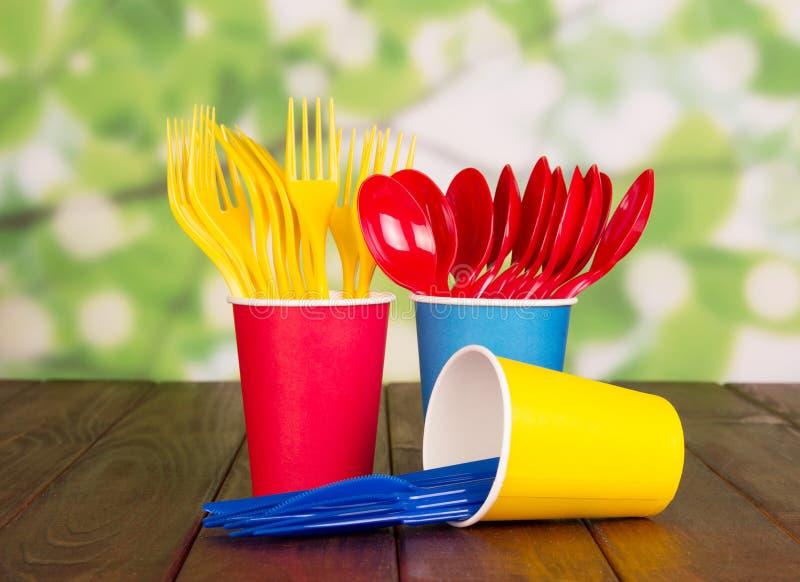 copos plásticos descartáveis Multi-coloridos, forquilhas, colheres no sumário verde foto de stock
