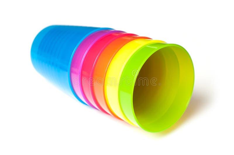 copos plásticos do bebê colorido no fundo branco imagem de stock
