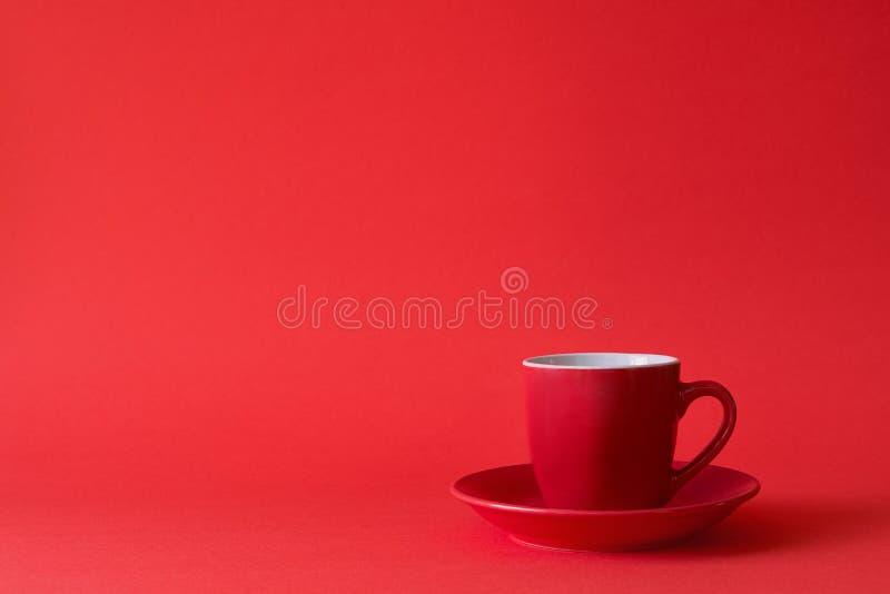 Copos vermelhos do chá ou do café no fundo de papel vermelho Copie o espaço foto de stock