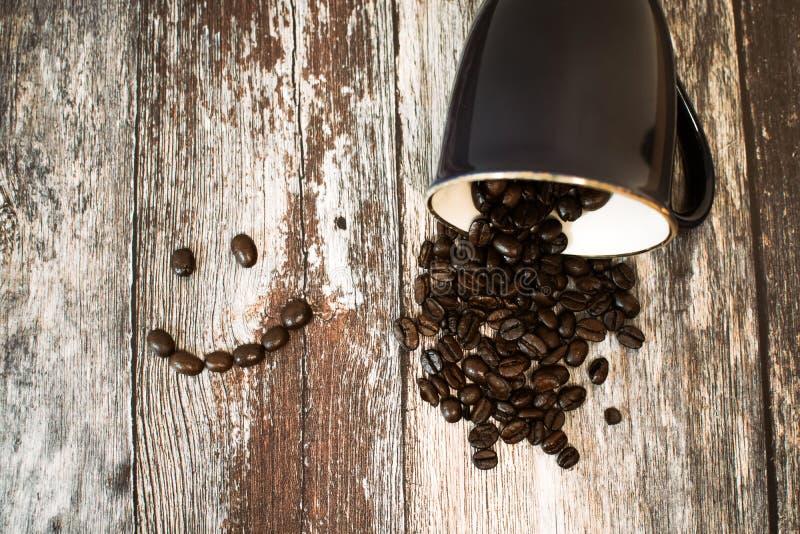 Coppa di ceramica nera con fagioli di caffè sulla superficie di legno marrone fotografia stock libera da diritti
