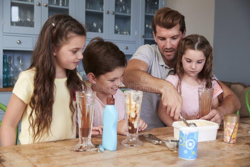 Coppe gelato di Making Ice Cream del padre con i bambini a casa fotografia stock