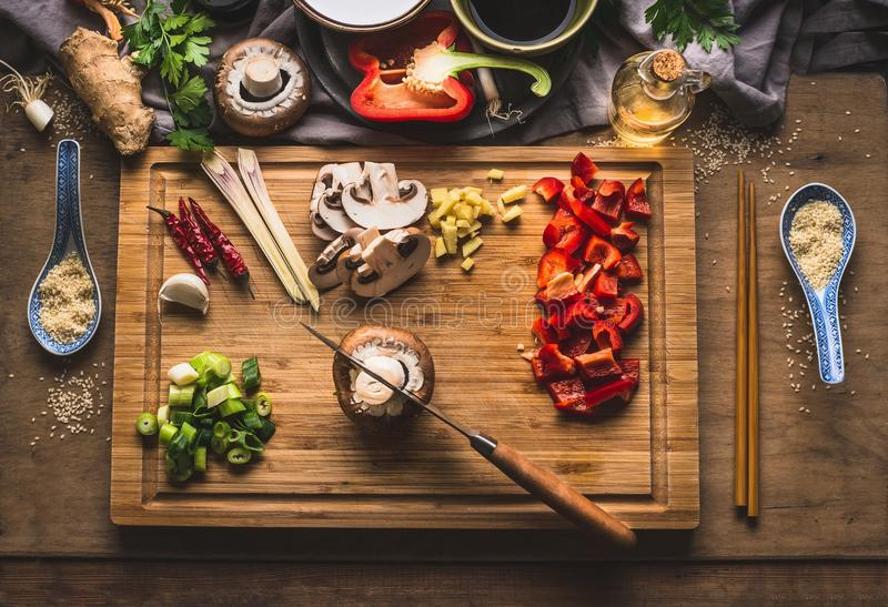 Copped vegetables ingredients for tasty vegetarian stir fry dishes on wooden cutting board with knife and chopsticks, top view. As stock images