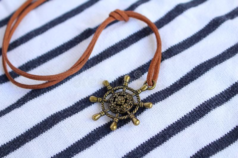 A copper boat bar pendant mounted on a leather lace royalty free stock photos