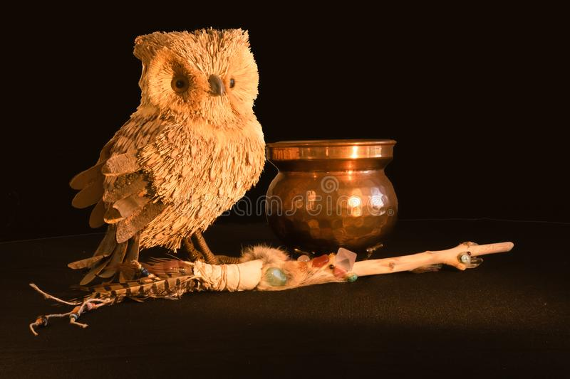 Copper cauldron, a magic wand with quartz and amethyst crystals and an owl made from natural material on a black background, spook royalty free stock photos