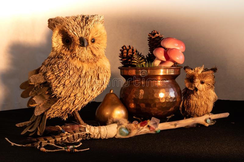 Copper cauldron with mushrooms and pine cones, a magic wand with quartz and amethyst crystals, a gold pear and an owl mother and c stock image