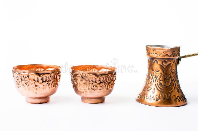 Copper coffee pot and cups isolated. On white stock photography