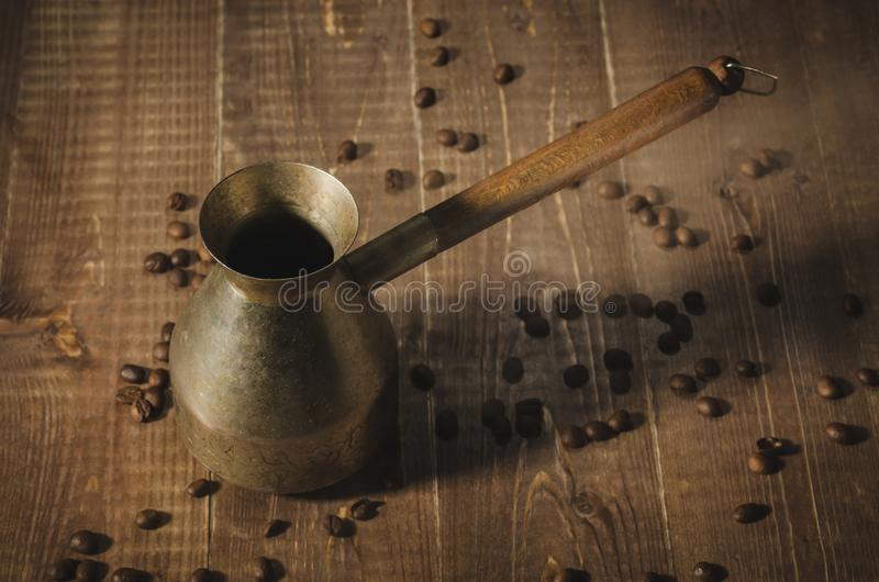 Copper coffee pot on a wooden background/copper coffee pot on a brown wooden background and coffee beans. Top view stock images