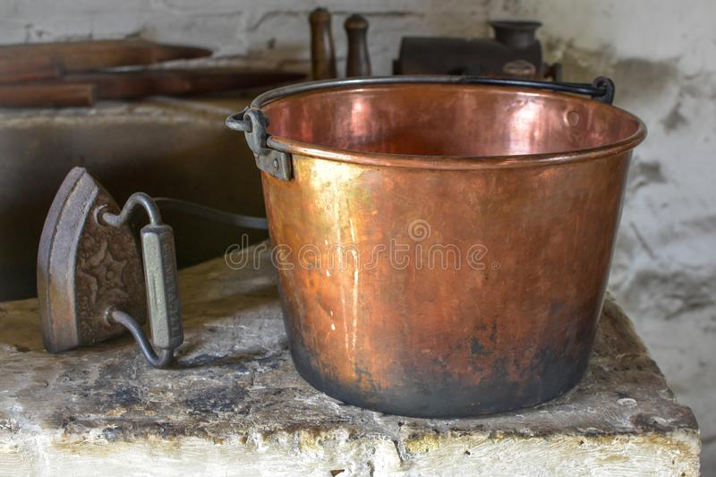 Copper Pail and Antique Iron. A copper colored pail with an antique iron sitting on a shelf at Old World Wisconsin, a living history museum in Eagle, WI royalty free stock photography