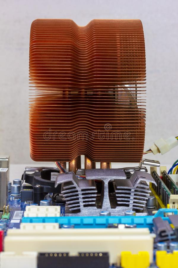 Copper CPU cooling system, chipset radiator and RAM in the slots on the motherboard. Side view close-up stock image