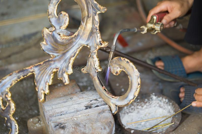 Copper handicraft and fine art products is being made manually by worker in Dai Bai traditional folk trade village, Vietnam stock photography
