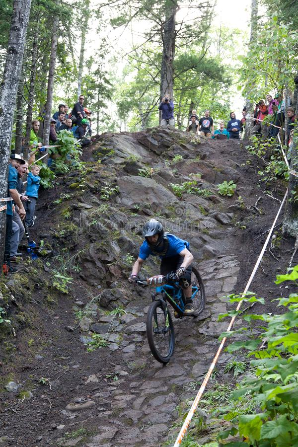 On 9/2/2017 in Copper Harbor, Michigan mountain biker launching from the cliff during enduro race. Annual Fat Tire Mountain Bike Festival in Copper Harbor stock images