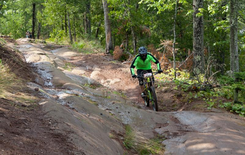 On 9/2/2017 in Copper Harbor, Michigan mountain biker riding on wet slick rock during enduro race. Annual Fat Tire Mountain Bike Festival in Copper Harbor stock photo