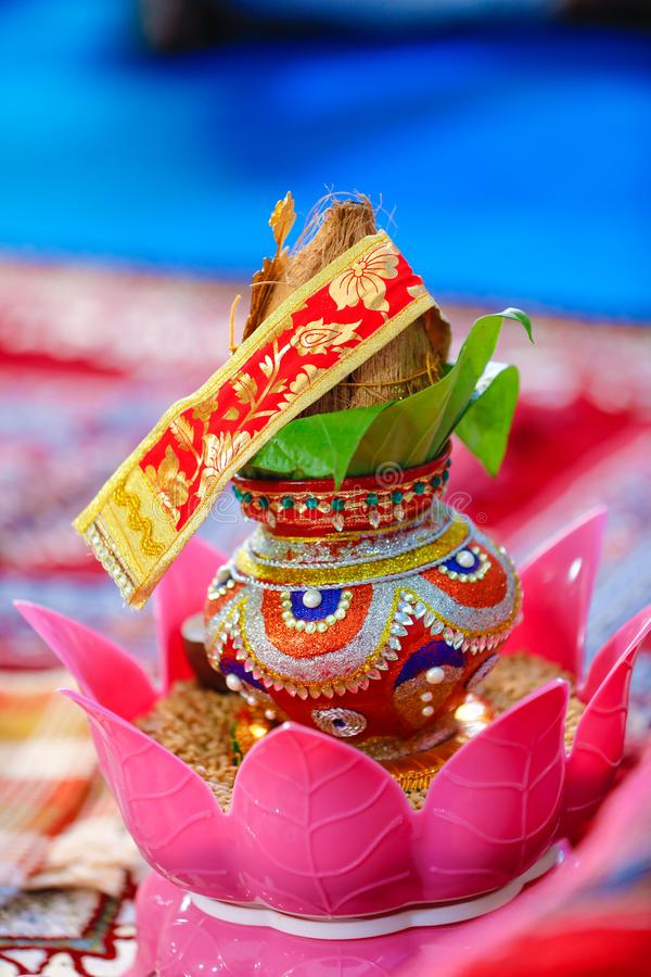 Copper kalash with coconut and mango leaf with floral decoration.  royalty free stock photos