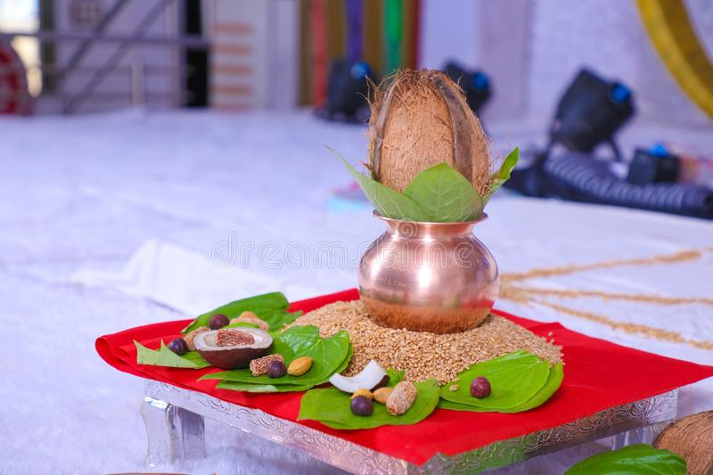 Copper kalash with coconut and mango leaf with floral decoration.  stock image