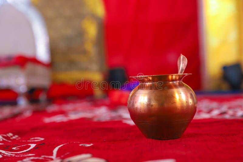 Copper kalash with coconut and mango leaf with floral decoration. Background beautiful brown celebration chestnut creative culture decorative deepawali design stock image