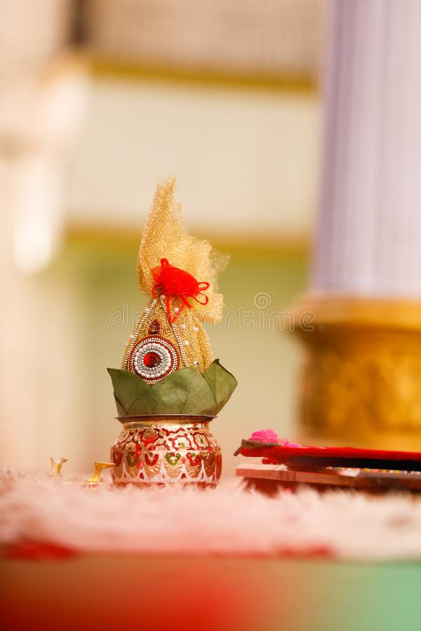 Copper kalash with coconut and mango leaf with floral decoration.  royalty free stock images