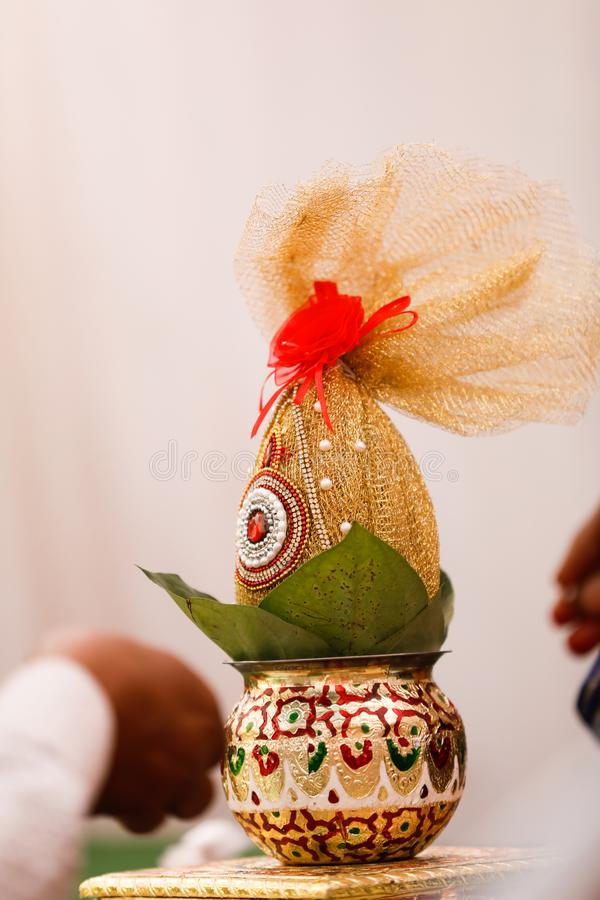 Copper kalash with coconut and mango leaf with floral decoration.  royalty free stock image