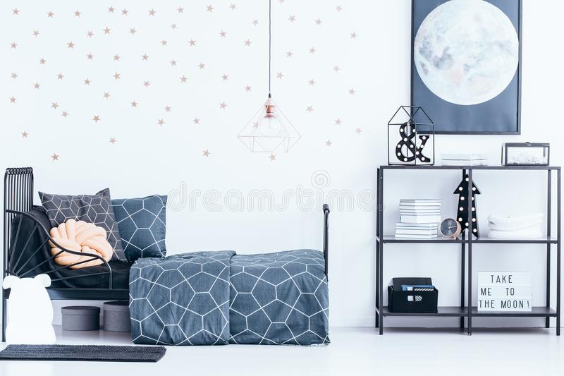 Gold wallpaper in teenager`s bedroom. Copper lamp above metal bed with navy blue bedsheets standing against white wall with gold stars wallpaper in bright stock photography