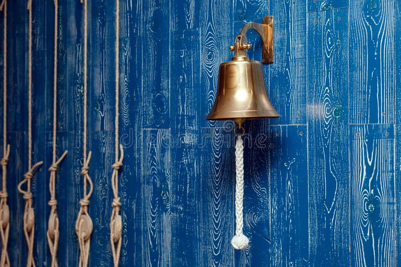 Copper old vintage bell, doorbell, rope on a wooden blue aged wall. Concept decor element in interior of deck, cabin of ship, royalty free stock photography