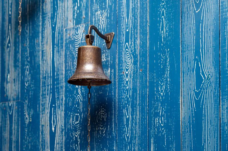 Copper old vintage bell, doorbell, rope on a wooden blue aged wall. Concept decor element in interior of deck, cabin of ship, stock photo