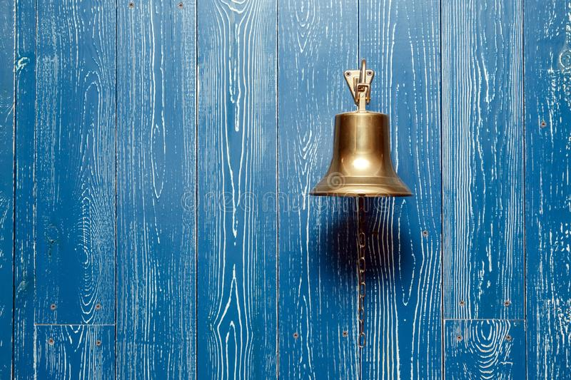 Copper old vintage bell, doorbell, rope on a wooden blue aged wall. Concept decor element in interior of deck, cabin of ship, royalty free stock images