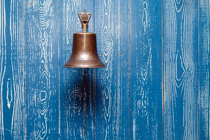 Copper old vintage bell, doorbell, rope on a wooden blue aged wall. Concept decor element in interior of deck, cabin of ship, royalty free stock image