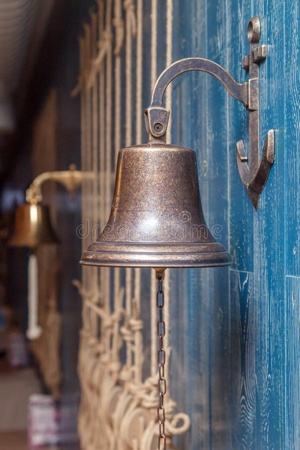Copper old vintage bell, doorbell, rope on a wooden blue aged wall. Concept decor element in interior of deck, cabin of ship, stock image