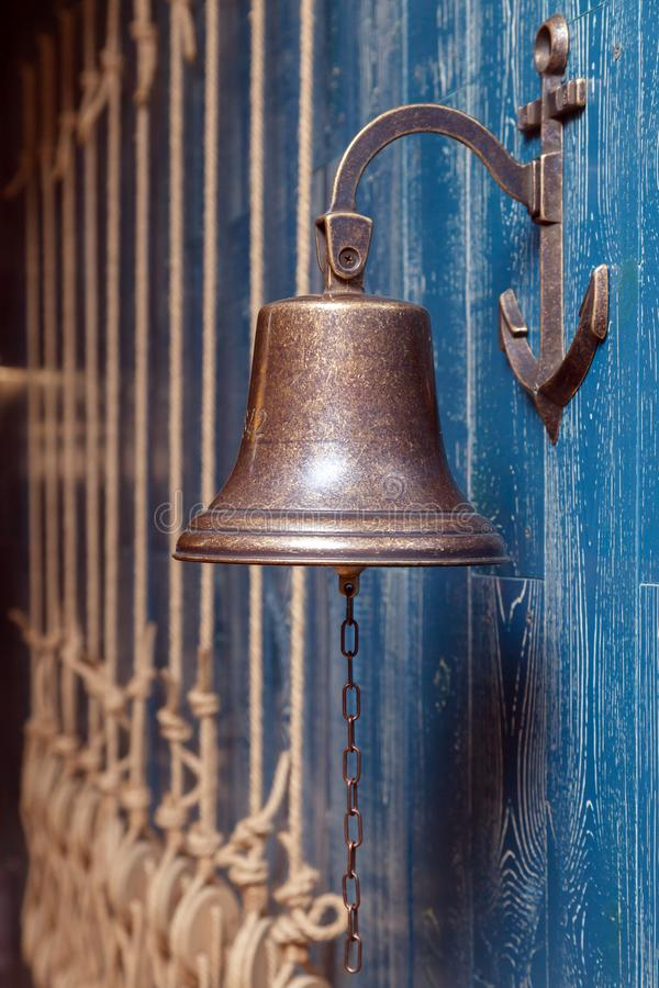 Copper old vintage bell, doorbell, rope on a wooden blue aged wall. Concept decor element in interior of deck, cabin of ship, royalty free stock photos