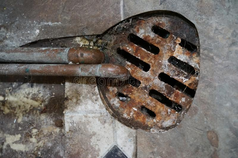 Rusty floor drain with copper  pipes stock photo